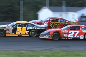 Wayne Helliwell, Jr. (27NH), Jimmy Hebert (58VT), and Brian Hoar (37VT) battle three wide for the lead at Airborne Speedway in the ACT 100 on Saturday night.  Hoar took over the point lead following his victory.  (Photo Credit: Leif Tillotson)