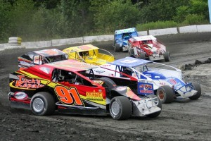 Tim Tucker (91) & Mike Dunn (9) lead a pack of SPortsman Modifieds off turn 4