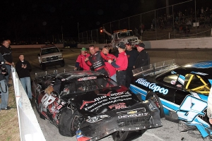 Jody Measamer (98)  climbs out of  his destroyed race car after tumbling down the front stretch